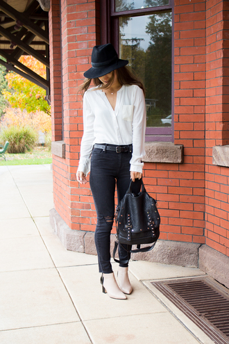 lana jayne blogger blouse jeans belt jewels shoes back to school black backpack white boots mid heel boots black hat felt hat hat wrap top white shirt shirt black jeans ripped jeans