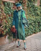 skirt,midi skirt,pleated skirt,satin,turtleneck sweater,coat,silk scarf,mid heel pumps,socks,handbag,sunglasses,fisherman cap
