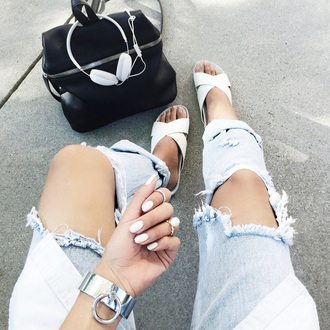 the haute pursuit jeans jewels bag ripped jeans slide shoes white shoes summer shoes ripped light blue jeans white nails silver bracelet black leather bag