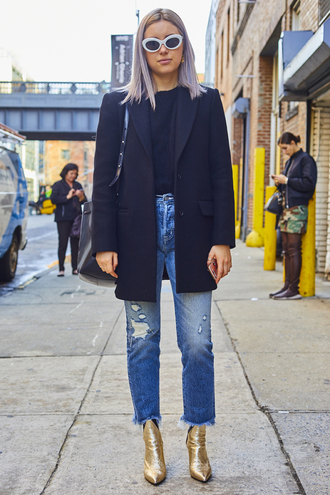 shoes nyfw 2017 fashion week 2017 fashion week streetstyle denim jeans blue jeans ripped jeans boots gold boots ankle boots metallic metallic shoes pointed boots coat black coat sweater black sweater sunglasses bag black bag winter outfits winter look