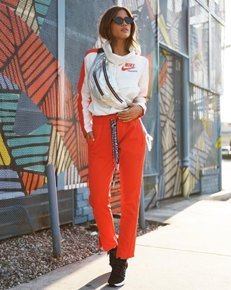 pants sweatpants orange sweatpants top white top bag metallic bag sunglasses sneakers fanny pack