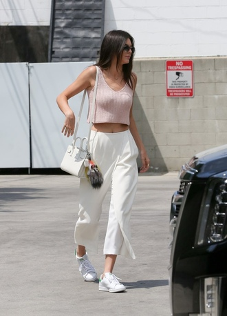 pants kendall jenner celebrity celebrity style cropped pants white pants top crop tops pink top sneakers white sneakers bag white bag summer top summer outfits sunglasses
