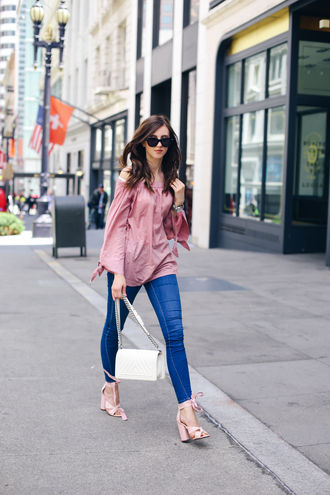 vogue haus blogger jeans shoes sunglasses jewels off the shoulder pink top long sleeves skinny jeans thick heel lace up heels pink heels white bag date outfit chanel boy bag boy bag chanel boy