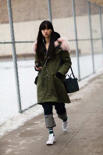 coat nyfw 2017 fashion week 2017 fashion week streetstyle green coat fur collar coat bag black bag denim jeans blue jeans socks sneakers low top sneakers white sneakers