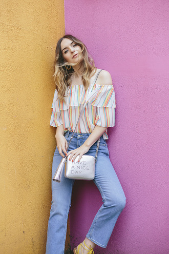 what olivia did... blogger off the shoulder off the shoulder top colorful stripes striped top shoulder bag metallic bag summer outfits flare jeans silver bag striped off shoulder top tassel blue jeans ruffle ruffled top