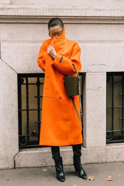 coat long coat orange coat green bag boots black boots sunglasses bag