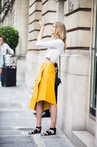 lefashion blogger skirt long sleeves white top yellow leather skirt crop tops flats shoulder bag yellow skirt asymmetrical skirt midi skirt high waisted skirt long sleeve crop top white crop tops sandals flat sandals black sandals spring outfits streetstyle american apparel max mara midi leather skirt