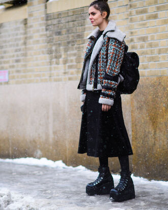 jacket tumblr nyfw 2017 streetstyle fashion week 2017 fashion week printed jacket shearling jacket black backpack backpack tights opaque tights boots black boots platform shoes skirt midi skirt black skirt winter outfits winter look