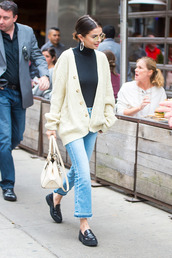 jeans,blue frayed jeans,white bag,selena gomez,black loafers,cream cable knit jumper,silver hoop earrings