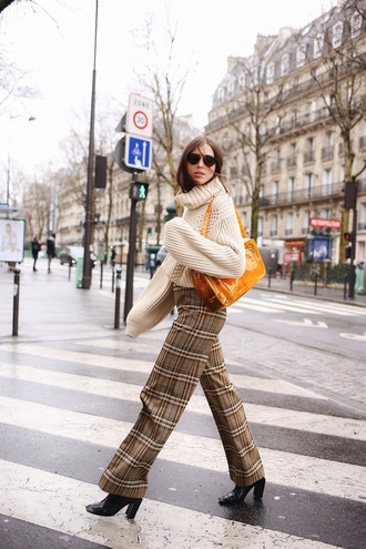 bag orange bag sweater beige pants plaid plaid pants boots black boots sunglasses