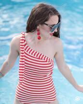 swimwear,one piece swimsuit,stripes,striped swimwear,asymmetrical,asymmetric swimsuit,earrings,pompon earrings,sunglasses,jewels
