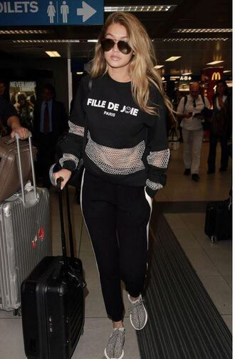 sweater sweatshirt mesh gigi hadid model streetstyle fashion week model off-duty graphic sweatshirt sweatpants black sweatpants mesh top celebrity style celebrity suitcase airport fashion shoes adidas yeezy black sunglasses style girl hair