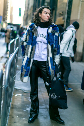 coat nyfw 2017 fashion week 2017 fashion week streetstyle printed fur coat printed coat fur coat faux fur coat pants black pants black leather pants leather pants flare pants boots black boots sweatshirt white sweater 00s style
