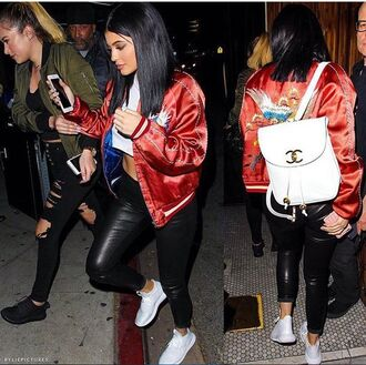 jacket bomber jacket kylie jenner redbomber bird bomber fashion black pants leather pants white t-shirt crop tops white crop tops nike running shoes white sneakers nike chanel bag backpack chanel backpack white purse chanel kardashians los angeles hollywood streetwear red bag shoes pants leather black patch embroidered red jacket