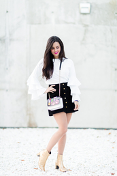 crimenes de la moda,blogger,coat,sunglasses,jewels,shoes,blouse,tumblr,white blouse,white top,ruffle,ruffled top,bell sleeves,skirt,mini skirt,black skirt,button up,button up skirt,boots,gold boots,ankle boots,mid heel boots,bag,printed bag