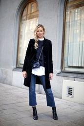 le fashion image,blogger,coat,top,bag,shoes,jeans,kick flare,kick flare jeans,blue jeans,black top,black coat,winter coat,boots,black boots,crossbody bag,black bag,cropped bootcut jeans,cropped bootcut blue jeans