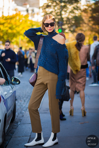 styledumonde blogger bag pants sweater sunglasses shoes blue sweater shoulder bag boots winter outfits tumblr cut-out shoulder top black sunglasses brown khaki pants cropped pants white boots ankle boots flat boots streetstyle