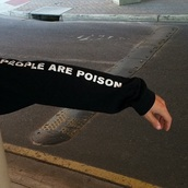 sweater,black,black and white word print,words on sweater,arm,people,people are poison