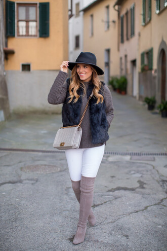 gal meets glam blogger hat bag white jeans faux fur vest knitted sweater thigh high boots