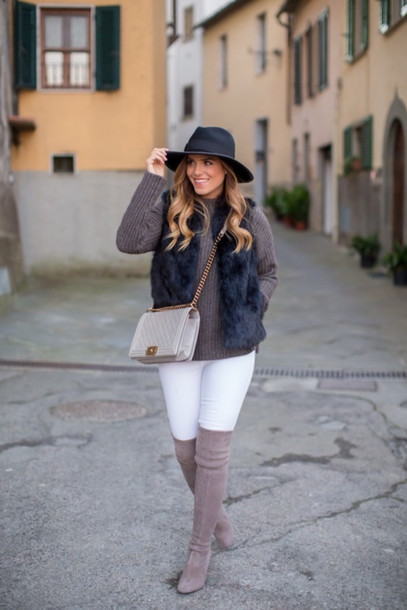 gal meets glam blogger hat bag white jeans faux fur vest knitted sweater thigh high boots black fur vest