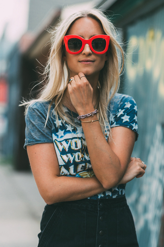the fashion guitar blogger red sunglasses oversized sunglasses graphic tee stars button up denim skirt summer outfits superheroes valentino wonder woman blue white red outfit