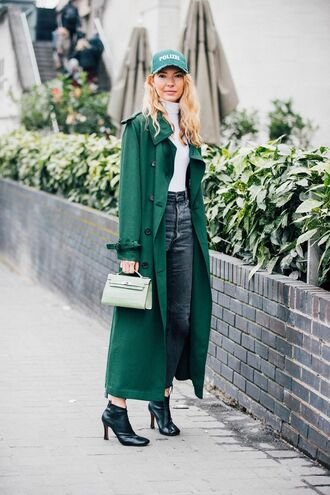 coat london fashion week 2017 fashion week 2017 fashion week streetstyle green green coat green long coat long coat bag boots black boots ankle boots denim jeans blue jeans sweater white sweater cap turtleneck sweater turtleneck mini bag