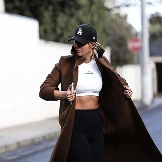 coat tumblr brown coat crop tops sports bra white top leggings black leggings cap black cap long coat athleisure sporty chic sportswear