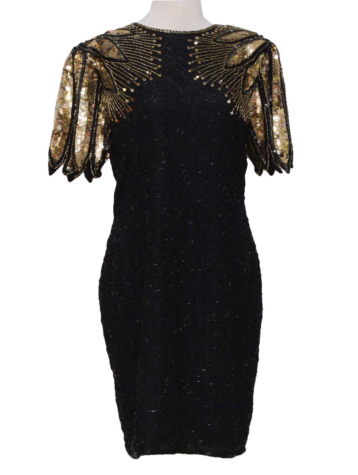Womens black background silk, polyester lined mid length, short sleeve totally 80s cocktail dress with thick shoulder pads, rounded neckline, tear drop style open back with hook tab closure above rear zip. dress has heavily beaded and sequins in gold and black with sharp leaf style design that evokes a butterflys wings along padded shoulders and down upper bodice. tight wiggle cut styling with rear slit along normally box cut hem.
