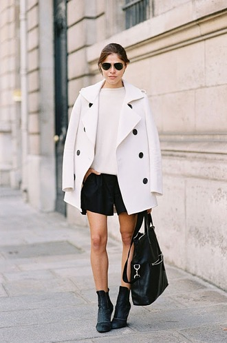 shoes white top white button coat black pleated shorts blak ankle boots black bag blogger sunglasses