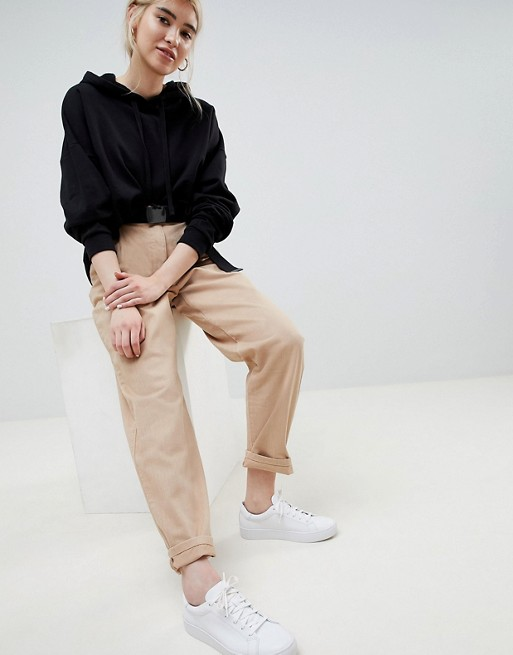 ASOS DESIGN tapered jeans with curved seams and belt in sand at asos.com