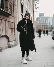 coat,black coat,white sneakers,black leggings,chanel bag,white top,long coat,knit,hat