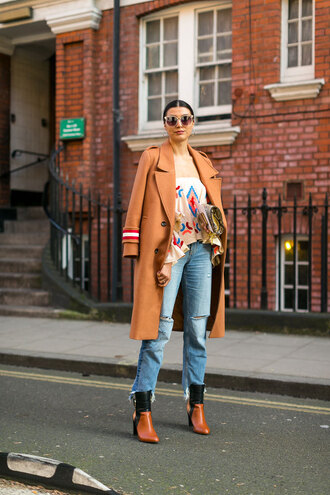 coat london fashion week 2017 fashion week 2017 fashion week streetstyle camel camel coat top off the shoulder off the shoulder top printed top denim jeans blue jeans cropped jeans boots brown boots high heels boots sunglasses