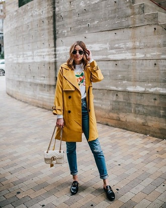 coat yellow coat sunglasses loafers black shoes bag white bag trench coat jeans black jeans denim shoes