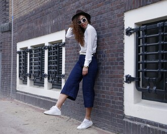 from hats to heels blogger jeans top hat sunglasses shoes jewels denim culottes blue pants palazzo pants white top long sleeves sneakers white sneakers low top sneakers