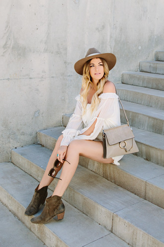 a little dash of darling blogger romper hat bag shoes sunglasses jewels off the shoulder white romper grey bag long sleeve romper chloe faye bag boots mid heel boots brown boots