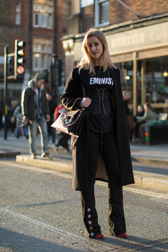 coat equa london fashion week 2017 fashion week 2017 fashion week streetstyle black coat all black everything corset t-shirt black t-shirt pants black pants flare pants bag black bag feminist tshirt