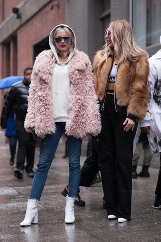 jacket nyfw 2017 fashion week 2017 fashion week streetstyle pink jacket fuzzy jacket hoodie white hoodie bomber jacket furry bomber jacket fur jacket faux fur jacket pants black pants sports bra boots white boots ankle boots denim jeans blue jeans sunglasses 00s style