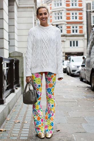 pants fashion week street style fashion week 2016 fashion week flare pants printed pants sweater white sweater bag printed bag shoes gold shoes fall outfits streetstyle