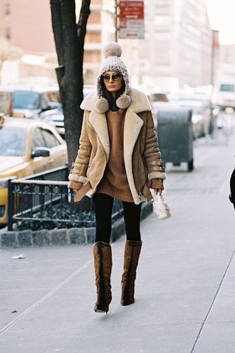 vanessa jackman blogger shearling jacket brown shearling jacket brown sweater brown jacket beanie pom pom beanie winter outfits winter coat furry boots high heels boots cat eye black sunglasses oversized sweater camel shearling coat cold weather outfit