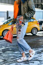 jeans,denim,patched denim,blue jeans,bomber jacket,green bomber jacket,orange bag,bag,top,black top,sneakers,white sneakers