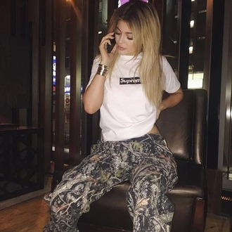 kardashians supreme white t-shirt kylie jenner jewelry bracelets stacked bracelets keeping up with the kardashians t-shirt supreme t-shirt kylie jenner fashion pants camo joggers camo pants camouflage joggers pants brown green joggers sweatpants