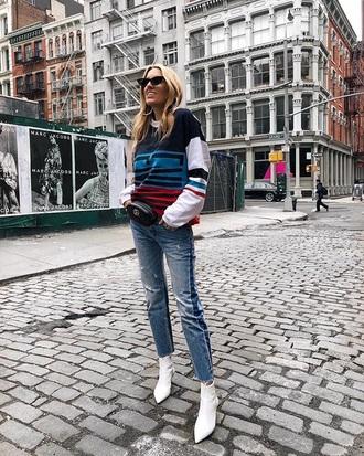 top white boots fanny pack belt bag bag sweatshirt multicolor blue jeans denim jeans boots sunglasses cat eye