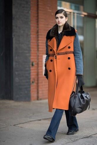 coat nyfw 2017 fashion week 2017 fashion week 2016 fashion week streetstyle orange orange coat bag black bag gloves jeans denim blue jeans flare jeans boots winter outfits winter look