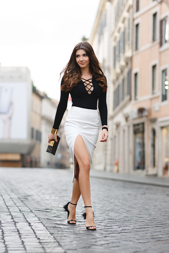 the mysterious girl blogger slit skirt lace up lace up top lace up bodysuit black bodysuit white skirt pencil skirt clutch sandals sandal heels high heel sandals fringe sandals date outfit long sleeve bodysuit