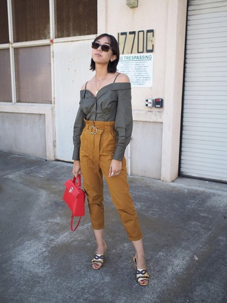 top green top sunglasses pants cropped pants bag red bag off the shoulder off the shoulder top