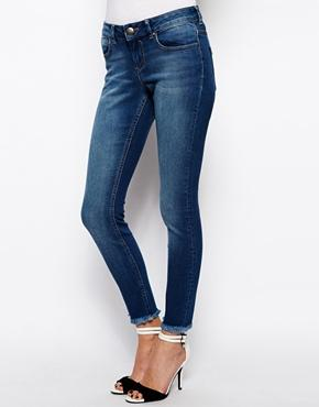 ASOS | ASOS Whitby Low Rise Skinny Ankle Grazer Jeans in Arizona Dark Wash Blue with Raw Hem at ASOS