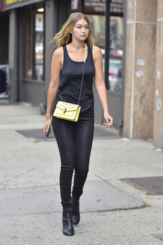 bag bvlgari serpenti bag bvlgari serpenti yellow yellow bag chain bag top black top black tank top tank top pants black pants black leather pants leather pants boots ankle boots black boots gigi hadid celebrity style celebrity model model off-duty bulgari serpenti bag