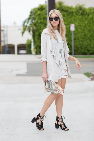 modern ensemble blogger shorts bag jacket shoes sunglasses lace up heels black heels denim shorts ripped shorts white jacket white top graphic tee clutch