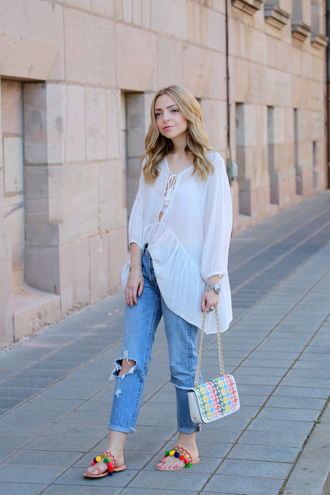 shirt asymmetric shirt white shirt jeans blue jeans ripped jeans sandals pom pom sandals flat sandals bag printed bag spring outfits