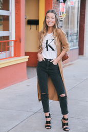the day book,blogger,ripped jeans,black jeans,calvin klein,black heels,beige jacket,stacked wood heels,black ripped jeans,quote on it,white t-shirt,camel coat,camel cardigan,logo,camel,logo tee